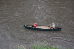 Photo of two people canoeing down the river.