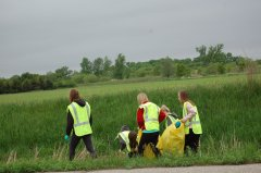 Photo of 2015 Adopt-A-Highway project - students picking up garbage from the ditch.