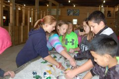 Photo of 2016 - Luverne students  reshaping the river in the stream table demonstration.